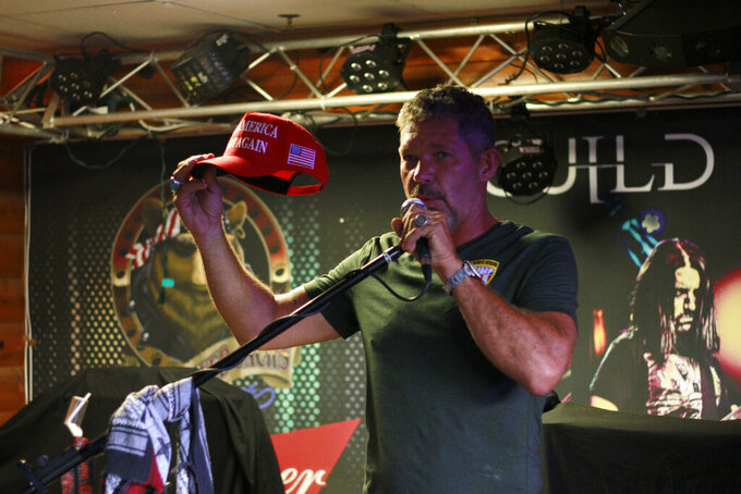 Chris Cox, founder of Bikers for Trump, holds up a Trump hat as he speaks at One Eyed Jack's Saloon in Sturgis, S.D., on Friday, Aug. 7, 2020. The group has taken advantage of recent motorcycle rallies, which have been some of the largest mass gatherings in the country, to make direct appeals to register to vote. While the group has gained a significant online following for its shows of bravado, it remains to be seen if they can get ballot boxes filled with bikers, many who hail from the suburbs.  (AP Photo/Stephen Groves)