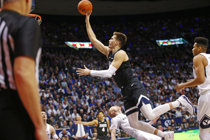 BYU guard TJ Haws, rear, falls as he defends against Gonzaga forward Filip Petrusev, center, during the first half during an NCAA college basketball game Saturday, Feb. 22, 2020, in Provo, Utah. (AP Photo/Rick Bowmer)