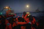 Migrants and refugees from different African nationalities react on an overcrowded wooden boat, as aid workers of the Spanish NGO Open Arms approach them in the Mediterranean Sea, international waters, off the Libyan coast, Friday, Jan. 10, 2020. (AP Photo/Santi Palacios)
