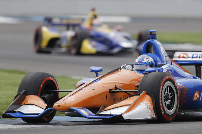 FILE - In this May 12, 2018, file photo, Scott Dixon, of New Zealand, heads through a turn during the IndyCar Grand Prix auto race at Indianapolis Motor Speedway in Indianapolis. NASCAR and IndyCar have postponed their weekend schedules at Atlanta Motor Speedway and St. Petersburg, Florida, due to concerns over the COVID-19 pandemic. NASCAR also postponed next week's race near Miami and IndyCar suspended the season through the end of April. (AP Photo/Darron Cummings, File)