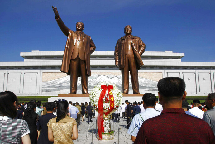 FILE - In this July 8, 2019, file photo, people visit Mansu Hill to pay tribute to the late leaders Kim Il Sung and Kim Jong Il on the occasion of the 25th anniversary of Kim Il Sung's death, in Pyongyang, North Korea. A panel monitoring U.N. sanctions said Monday, Aug. 5, that North Korean cyber experts have illegally raised money for the country's weapons of mass destruction programs