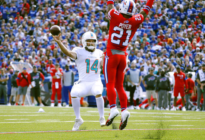 Miami Dolphins quarterback Ryan Fitzpatrick, left, passes under pressure from Buffalo Bills safety Jordan Poyer in the first half of an NFL football game, Sunday, Oct. 20, 2019, in Orchard Park, N.Y. (AP Photo/Ron Schwane)