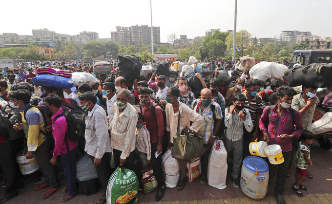 People wearing masks as a precaution against the coronavirus stand in queues to board trains at Lokmanya Tilak Terminus in Mumbai, India, Wednesday, April 14, 2021.Migrant workers are swarming rail stations in India's financial capital Mumbai to go to their home villages as virus-control measures dry up work in the hard-hit region. The government of Maharashtra state imposed lockdown-like curbs on Wednesday for 15 days to check the spread of the virus. It closed most industries, businesses and public places and limited the movement of people, but didn't stop the bus, train and air services. An exodus ensued, with panicked day laborers hauling backpacks onto overcrowded trains leaving Mumbai, travel that raises fears of infections spreading in rural areas. (AP Photo/Rafiq Maqbool)