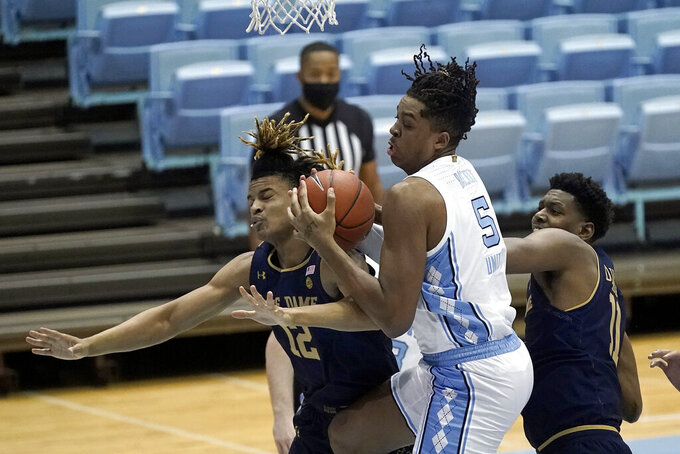 North Carolina forward Armando Bacot (5) struggles for a rebound with Notre Dame guard Tony Sanders Jr. (12) and forward Juwan Durham (11) during the first half of an NCAA college basketball game in Chapel Hill, N.C., Saturday, Jan. 2, 2021. (AP Photo/Gerry Broome)
