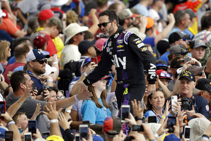 Jimmie Johnson shakes hands with fans during driver introductions before the NASCAR Daytona 500 auto race Sunday, Feb. 16, 2020, at Daytona International Speedway in Daytona Beach, Fla. Johnson is making his last Daytona 500 start. (AP Photo/Chris O'Meara)
