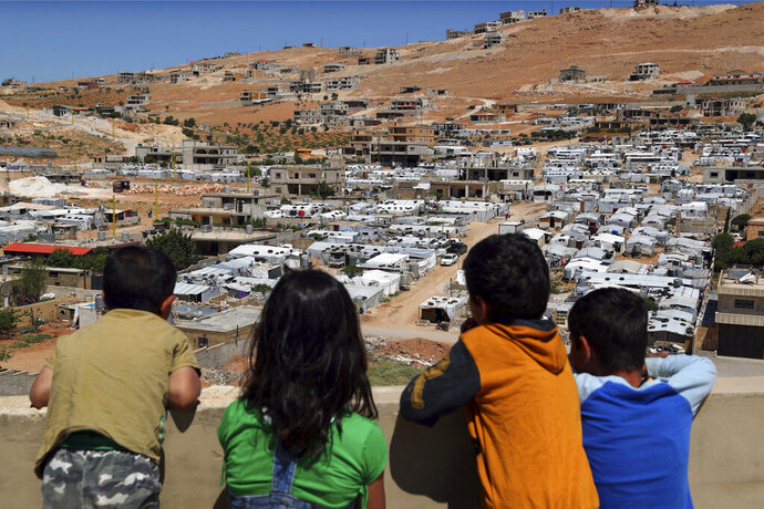 In this Sunday, June 16, 2019 photo, Lebanese children look from the rooftop of their home at a Syrian camp in the eastern Lebanese border town of Arsal, Lebanon. Authorities in Lebanon are waging their most aggressive campaign yet against Syrian refugees, making heated calls for them to go back to their country and taking action to ensure they can't put down roots. They are shutting down shops where Syrians work without permits and ordering the demolition of anything in their squalid camps that could be a permanent home. (AP Photo/Bilal Hussein)