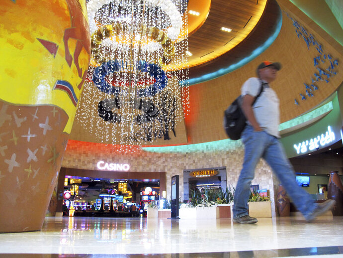 A man walks through the lobby of the Navajo Nation's Twin Arrows Casino, east of Flagstaff, Ariz., Tuesday, May 15, 2018. American Indian tribes are welcoming the opportunity to add sports betting to potentially hundreds of casinos across the country after the U.S. Supreme Court cleared the way for states to legalize it. (AP Photo/Felicia Fonseca)