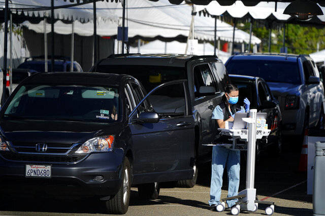 People wait in cars for a vaccination against the coronavirus at a new