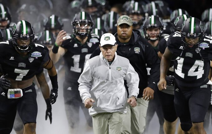 FILE - In this Dec. 2, 2016, file photo, Ohio head coach Frank Solich runs out onto the field with his team before the Mid-American Conference championship NCAA college football game against Western Michigan, in Detroit. Solich is expected to become the Mid-American Conference's all-time winning coach this season. The former Nebraska coach has won 106 games with the Bobcats over 15 years since Nebraska fired him following a nine-win season. (AP Photo/Carlos Osorio, File)