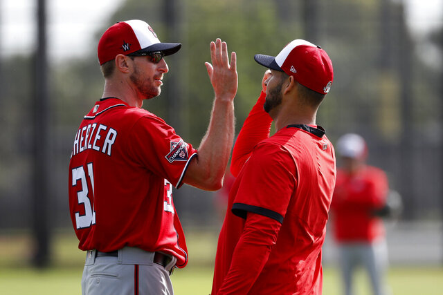 Washington Nationals pitcher Max Scherzer, left, gets a high-five from fellow pitcher Anibal Sanchez during spring training baseball practice Friday, Feb. 14, 2020, in West Palm Beach, Fla. (AP Photo/Jeff Roberson)
