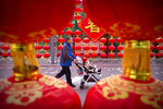 A man pushes a child in a stroller wearing a face mask past decorations for a canceled Lunar New Year temple fair at Longtan Park in Beijing, Saturday, Jan. 25, 2020. China's most festive holiday began in the shadow of a worrying new virus Saturday as the death toll surpassed 40, an unprecedented lockdown kept 36 million people from traveling and authorities canceled a host of Lunar New Year events. (AP Photo/Mark Schiefelbein)