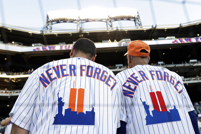New York Mets fans wear jerseys to remember the 20th anniversary of the 9/11 terrorist attacks before a baseball game against the New York Yankees on Saturday, Sept. 11, 2021, in New York. (AP Photo/Adam Hunger)