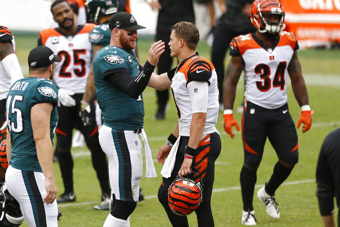 Philadelphia Eagles' Carson Wentz, left, and Cincinnati Bengals' Joe Burrow meet after an NFL football game, Sunday, Sept. 27, 2020, in Philadelphia. (AP Photo/Laurence Kesterson)