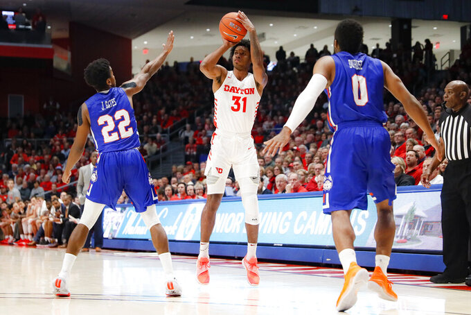 Dayton's Jhery Matos (31) shoots over Houston Baptist's Jalon Gates (22) during the first half of an NCAA college basketball game, Tuesday, Dec. 3, 2019, in Dayton, Ohio. (AP Photo/John Minchillo)