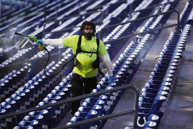 A stadium workers sprays disinfectant over the seats after a college basketball game between Baylor and Hartford in the first round of the NCAA tournament at Lucas Oil Stadium Friday, March 19, 2021, in Indianapolis. (AP Photo/Mark Humphrey)