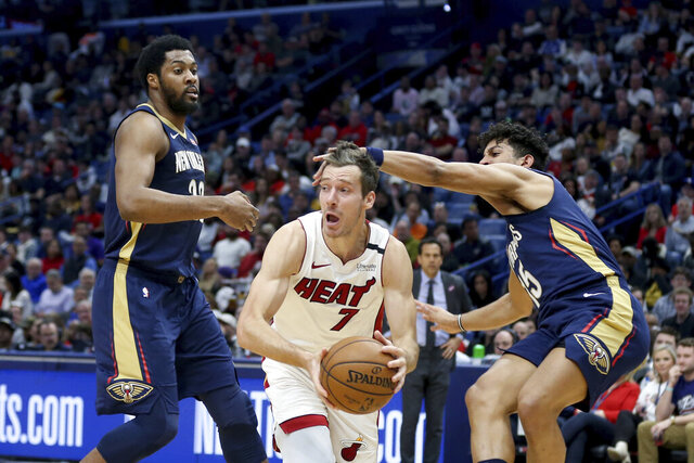 Miami Heat guard Goran Dragic (7) looks to pass the ball as New Orleans Pelicans center Derrick Favors (22) and guard Frank Jackson (15) defend during the first half of an NBA basketball game in New Orleans, Friday, March 6, 2020. (AP Photo/Rusty Costanza)