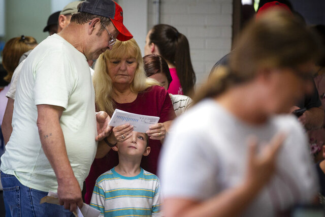 FILE- In this July 15, 2019 file photo, Darrell Raleigh, from left, Donna Raleigh and their grandson, Daniel Lowe, 5, look over their utility bills as they wait in the Holy Trinity Church in Harlan, Ky., hopeful of having their electric bills paid for by the Catholic Church. Sichko handed out more than $20,000 to miners who are struggling to pay bills after the coal company they work for filed for bankruptcy protection. This was one of the top stories in Kentucky in 2019. (Alton Strupp/Courier Journal via AP, File)