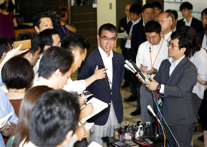 Japan's Foreign Minister Taro Kono, center, speaks to the media after meeting with South Korean Ambassador to Japan Nam Gwan Pyo, at foreign ministry in Tokyo Friday, July 19, 2019. Japan has summoned South Korea's ambassador to protest Seoul's refusal to join in an arbitration panel to settle a dispute over World War II labor. (Masanobu Kumagai/Kyodo News via AP)