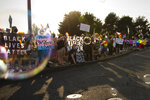 Protesters against a new school policy that bans Black Lives Matter and Pride flags across Newberg School District facilities wave at cars entering and leaving Newberg, Ore., on Aug. 24, 2021.  The policy has prompted a torrent of recriminations and threats to boycott the town and its businesses. (Jozie Donaghey/The Oregonian via AP)