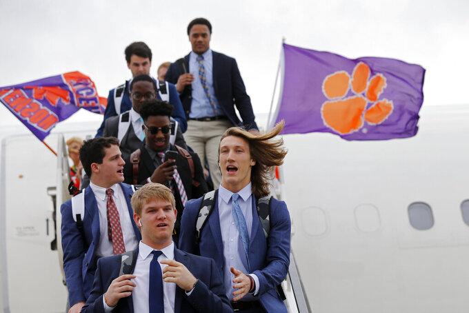 Clemson quarterback Trevor Lawrence, right front, arrives with the team in New Orleans for the NCAA College Football Playoff title game, Friday, Jan. 10, 2020. Clemson is scheduled to play LSU on Monday. (AP Photo/Gerald Herbert)