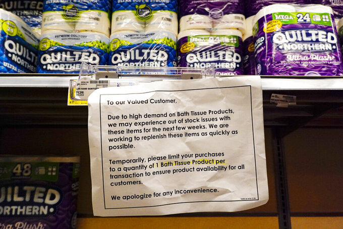A sign displays limits on the amount of bath tissue that can be purchased at a Kroger Store in Carmel, Ind., Tuesday, Nov. 17, 2020. A surge of new coronavirus cases in the U.S. is sending people back to stores to stockpile again, leaving shelves bare and forcing retailers to put limits on purchases. (AP Photo/Michael Conroy)