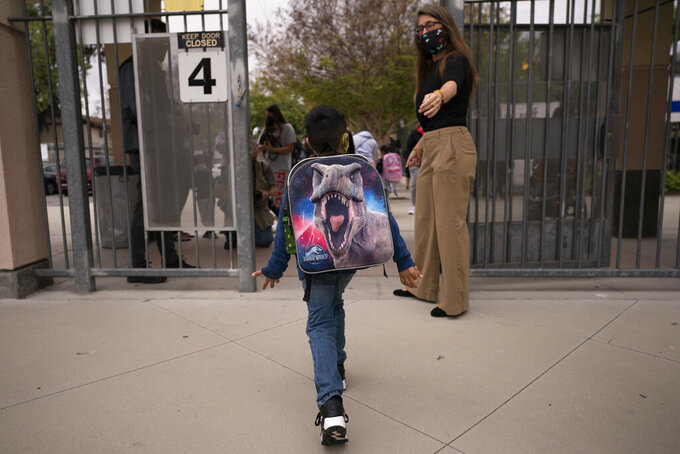 Kindergartener Angel Hernandez leaves after the first day of in-person learning at Maurice Sendak Elementary School in Los Angeles, Tuesday, April 13, 2021. More than a year after the pandemic forced all of California's schools to close classroom doors, some of the state's largest school districts are slowly beginning to reopen this week for in-person instruction. (AP Photo/Jae C. Hong)