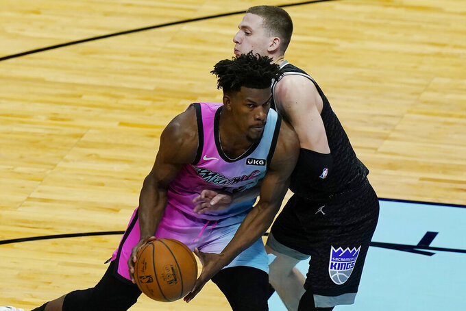 Sacramento Kings guard Kyle Guy (7) defends Miami Heat forward Jimmy Butler (22) during the second half of an NBA basketball game, Saturday, Jan. 30, 2021, in Miami. (AP Photo/Marta Lavandier)
