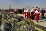 FILE - In this Jan. 8, 2020, file photo, rescue workers carry the body of a victim of a Ukrainian plane crash in Shahedshahr, southwest of the capital Tehran, Iran. The downing of a Ukrainian jetliner near Tehran on Jan. 8 highlights the limits of the civilian arm of Iran's government against the absolute power of the Shiite theocracy and the paramilitary forces beneath it. (AP Photo/Ebrahim Noroozi, File)