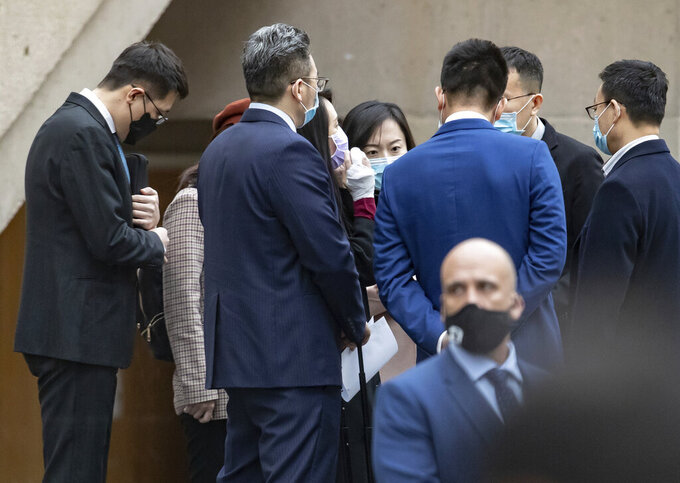 Chief Financial Officer of Huawei, Meng Wanzhou, centre, is seen with a bandaged middle finger and hand as she meets with colleagues during a break from a hearing at British Columbia Supreme Court, in Vancouver, British Columbia, Friday, March 19, 2021. (Darryl Dyck/The Canadian Press via AP)