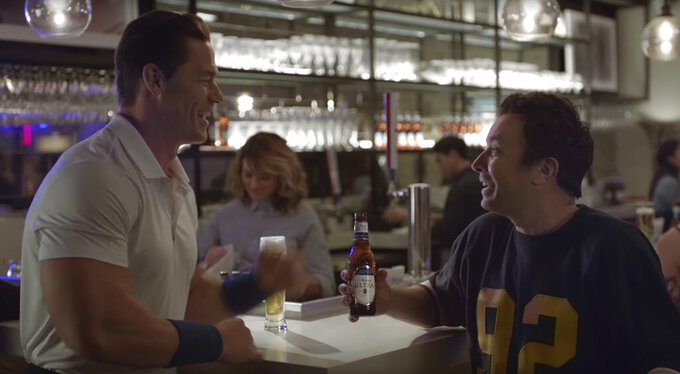 """This undated image provided by Michelob ULTRA shows John Cena, left, and Jimmy Fallon in a scene from the company's 2020 Super Bowl NFL football spot. Wrestler-turned-actor John Cena tries to convince Tonight Show host Jimmy Fallon that there's a """"lighter side"""" to working out, with cameos by Tonight show band The Roots and runner Usain Bolt. (Michelob ULTRA via AP)"""