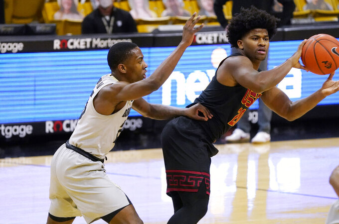 Southern California guard Ethan Anderson, right, passes the ball as Colorado guard McKinley Wright IV defends during the first half of an NCAA college basketball game Thursday, Feb. 25, 2021, in Boulder, Colo. (AP Photo/David Zalubowski)