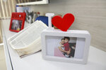 A framed photo shows Esther Melo da Silva with her grandson, in Manaus, Brazil, Tuesday, Aug. 4, 2020. The 67-year-old grandmother reported having a cold, and a few days later started having problems breathing. She died from COVID-19 on April 9, after five days in a public hospital. (AP Photo/Helton Belo)