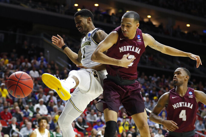 Michigan guard Charles Matthews, left, fights for a loose ball with Montana's Kendal Manuel and Sayeed Pridgett (4) during a first round men's college basketball game in the NCAA Tournament, Thursday, March 21, 2019, in Des Moines, Iowa. (AP Photo/Charlie Neibergall)