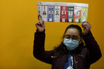 An electoral official holds a ballot as they count votes after polls closed for general elections in La Paz, Bolivia, Sunday, Oct. 18, 2020. (AP Photo/Juan Karita)