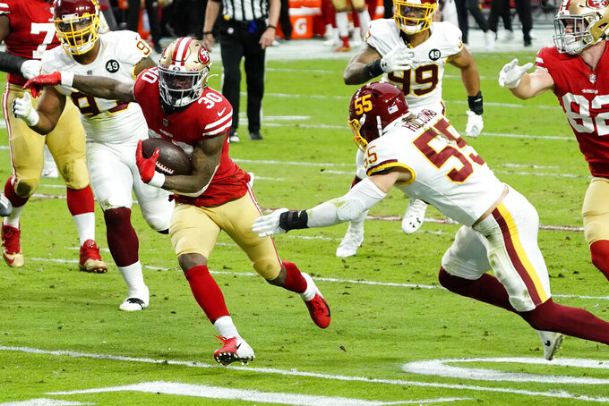 San Francisco 49ers running back Jeff Wilson (30) tries to avoid Washington Football Team linebacker Cole Holcomb (55) during the first half of an NFL football game, Sunday, Dec. 13, 2020, in Glendale, Ariz. (AP Photo/Rick Scuteri)