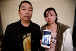 FILE- In this Nov. 1, 2017 file photo, Ronggao Zhang, left, and Lifeng Ye, display a photo them with their missing daughter, Yingying Zhang, in Urbana, Ill. Almost two years after their daughter disappeared from the University of Illinois campus, the parents of visiting Chinese scholar Yingying Zhang are back in Champaign-Urbana for the trial of her accused killer. Former Illinois student Brendt Christensen is charged with  Zheng, whose body hasn't been found. He pleaded not guilty and his trial is set to begin Monday, June 3, 2019. (AP Photo/Michael Conroy File)