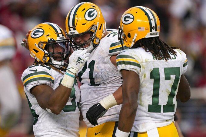Green Bay Packers running back Aaron Jones, left, is congratulated by center Josh Myers, middle, and wide receiver Davante Adams (17) after scoring against the San Francisco 49ers during the first half of an NFL football game in Santa Clara, Calif., Sunday, Sept. 26, 2021. (AP Photo/Tony Avelar)