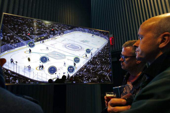 People watch real-time puck and player tracking technology on display during an NHL hockey game between the Vegas Golden Knights and the San Jose Sharks, in Las Vegas, Thursday, Jan. 10, 2019. The NHL for the first time has tested real-time puck and player tracking in regular-season games with the aim of having it ready for the 2019-20 season. Microchips were added to players' shoulder pads and fitted inside specially designed pucks for two Vegas Golden Knights home games this week: Tuesday against the New York Rangers and Thursday against the San Jose Sharks. Antennas stationed around the arena tracked the players and the puck through radio frequencies and beamed the data to a suite where league and Players' Association executives and representatives from 20 teams and various technology firms, sports betting companies and TV rights holders were on hand for the two nights of testing.(AP Photo/John Locher)