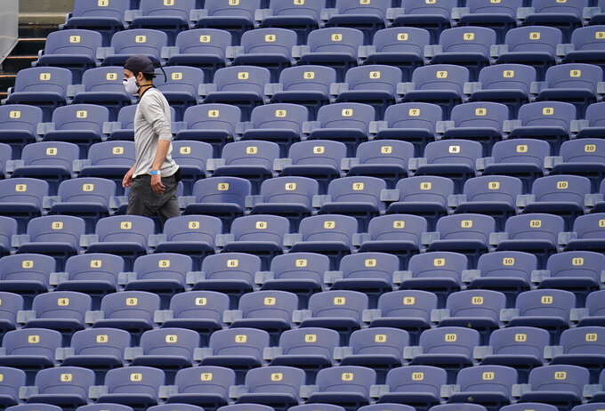 A worker cuts through the seats as the Denver Broncos take part in drills during an NFL football practice in empty Empower Field at Mile High, Saturday, Aug. 29, 2020, in Denver. (AP Photo/David Zalubowski)
