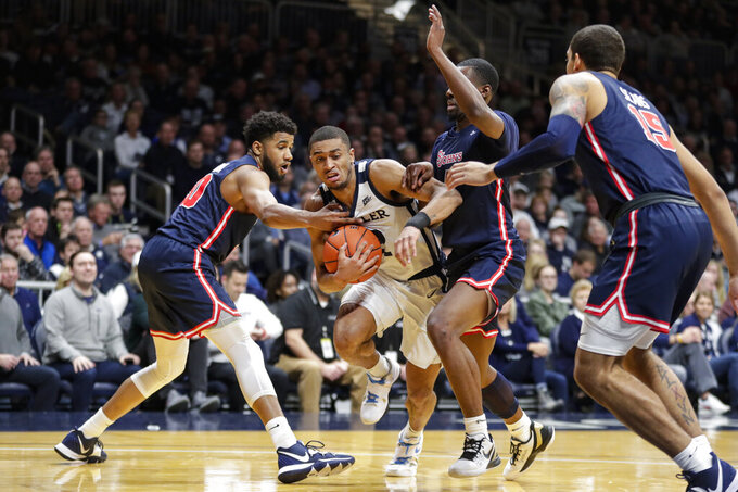 Butler guard Aaron Thompson (2) cuts between St. John's guard LJ Figueroa (30) and guard Greg Williams Jr. (4) during the first half of an NCAA college basketball game in Indianapolis, Wednesday, March 4, 2020. (AP Photo/Michael Conroy)