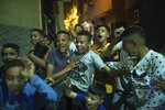 In this Monday, Sept. 9, 2019 photo, youths and children react during the celebration of Ashura, in Sale, near Rabat, Morocco. On Sept. 9, the Arab and Muslim world marked Ashura, a day commemorating the death of Imam Hussein, the grandson of the Prophet Muhammad and one of Shia Islam's most important figures. (AP Photo/Mosa'ab Elshamy)