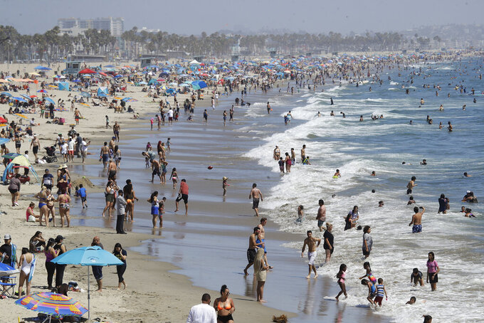 FILE - In this July 12, 2020, file photo, visitors crowd the beach in Santa Monica, Calif., amid the coronavirus pandemic. Californians headed to campgrounds, beaches and restaurants over the long holiday weekend as the state prepared to shed some of its coronavirus rules. (AP Photo/Marcio Jose Sanchez, File)