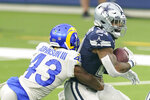 Dallas Cowboys running back Ezekiel Elliott, right, is tackled by Los Angeles Rams safety John Johnson III during the first half of an NFL football game Sunday, Sept. 13, 2020, in Inglewood, Calif. (AP Photo/Ashley Landis )