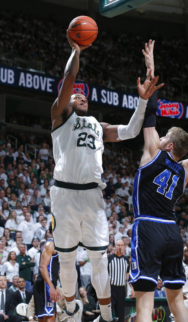 Michigan State's Xavier Tillman, left, shoots against Duke's Jack White during the second half of an NCAA college basketball game, Tuesday, Dec. 3, 2019, in East Lansing, Mich. (AP Photo/Al Goldis)