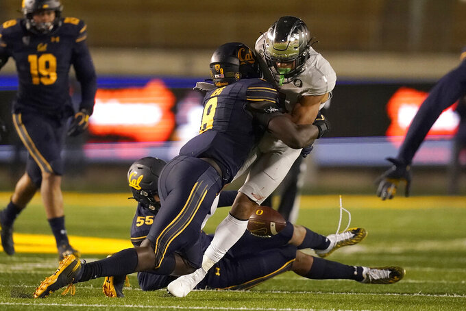 Oregon wide receiver Johnny Johnson III, center right, fumbles the ball as he is hit by California linebacker Kuony Deng (8) during the second half of an NCAA college football game in Berkeley, Calif., Saturday, Dec. 5, 2020. California recovered the ball. (AP Photo/Jeff Chiu)