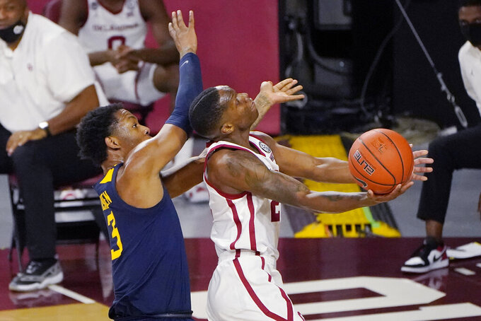 Oklahoma guard Umoja Gibson (2) goes to the basket in front of West Virginia forward Gabe Osabuohien (3) in the second half of an NCAA college basketball game Saturday, Jan. 2, 2021, in Norman, Okla. (AP Photo/Sue Ogrocki)