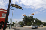 In this Aug. 5, 2019, photo, a vehicle makes its' way through an intersection in the town square in Mount Vernon, Texas. Former NBA player Greg Ostertag and his wife Shannon have spearheaded the town's recent revitalization from what used to be boarded-up buildings. The small East Texas community is also where Art Briles is coaching football again. (AP Photo/Tony Gutierrez)