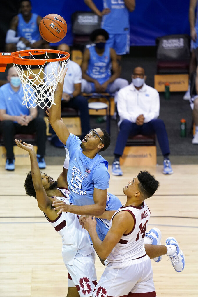 North Carolina forward Garrison Brooks (15) leaps to the basket over Stanford guard Bryce Wills (2) and forward Spencer Jones (14) during the second half of an NCAA college basketball game in the semifinals of the Maui Invitational, Tuesday, Dec.1, 2020, in Asheville, N.C. (AP Photo/Kathy Kmonicek)