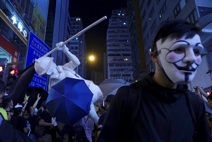 A protester with a mask stands near other protesters moving a statue depicting a protester armed with gas mask, helmet and umbrella on the streets of Hong Kong on Friday, Oct. 4, 2019. Masked protesters streamed into Hong Kong streets Friday after the city's embattled leader invoked rarely used emergency powers to ban masks at rallies in a hardening of the government's stance after four months of anti-government demonstrations. (AP Photo/Vincent Yu)