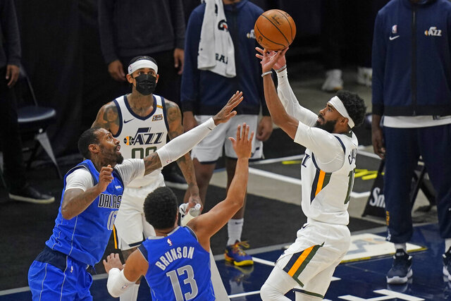 Dallas Mavericks' James Johnson, left, and Jalen Brunson (13) defend as Utah Jazz guard Mike Conley, right, shoots in the first half during an NBA basketball game Wednesday, Jan. 27, 2021, in Salt Lake City. (AP Photo/Rick Bowmer)